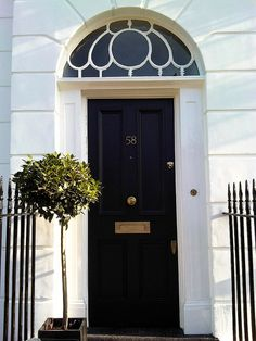 London front door painted in black eggshell - Amazing what some greenery will do