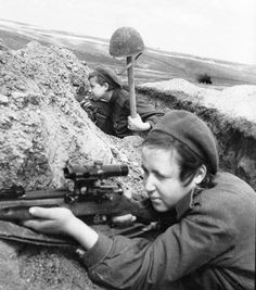 """Soviet Army female snipers out on the hunt. A helmet on a stake serves as the  lure. The sniper nearer the camera would take the shot if a German rises to aim at the Russian """"soldier."""""""