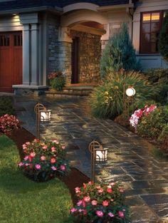 C'est le jardin a l'arriere de la maison. Il y a un sentier en bloc, des fleurs et des lanternes des deux cotes.