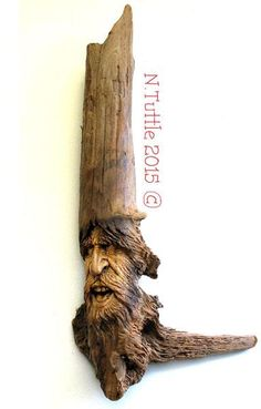 """""""Defying Destiny""""     23 inches tall, 11 inches across his greatest   width and weighs in at more than four pounds!   This wood spirit hangs showing off his ¾ profile.  Signed and dated:   N. Tuttle 5/19/15"""