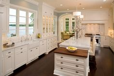 Beautiful kitchen with creamy white kitchen cabinets, with marble countertops, farmhouse sink, slate blue walls paint color and white kitchen island with black walnut butcher block drop down cabinet.