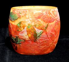 A stunning and dramatically acid etched DAUM pillow vase with a design of Autumn leaves and berries raised on a frosted ground.  The ground colour for this Daum pillow vase is a vitrified mottle of reds, crimson, yellow, green and orange giving a vibrant image of autumn colours. The surface design is polished and is a typical example of the later vitrified Daum vases that continued into the Art Deco period.From website: Art Nouveau Glass Specialist dealer in Galle, Daum and Lalique Glass