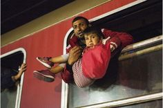 A man holds a child in a train heading to Serbia from the Macedonian-Greek border near Gevgelija