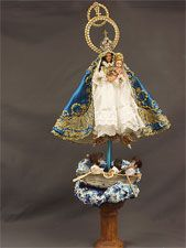 Barbie Dressed as La Virgen de la Caridad del Cobre, Patron Saint of Cuba: Doll wears ornate blue and gold robe characteristic of the Virgin Mary, has a crown, is holding a baby representing the image of Jesus, an orb and a crucifix. Below the doll is a paper boat on painted cloth representing the sea, with three figures on the boat meant to be fishermen lost at sea whom the Virgin saves. 3 angels are suspended above the boat. Made by Armando Pérez, a man of Cuban descent.
