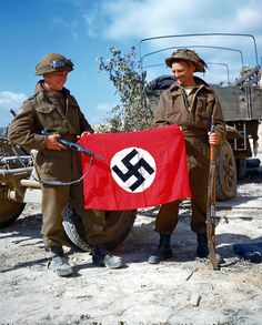Two soldiers of the Third Canadian Division displaying a captured Nazi flag in Normandy.
