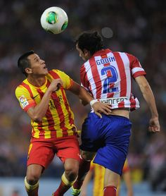 Alexis Sanchez (L) of Barcelona  heads the ball beside Diego Godin of Atletico de Madrid during the Spanish Super Cup first leg match between Atletico de Madrid and Barcelona at Vicente Calderon Stadium on August 21, 2013 in Madrid, Spain.