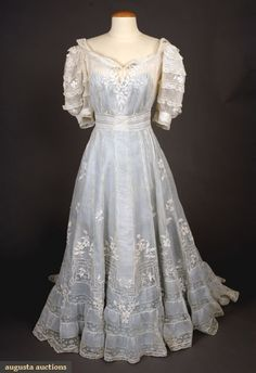 "EMBROIDERED LACE TEA GOWN, c. 1905 Fine cotton batiste w/ Val lace insertions & raised floral allover embroidery, back buttons, Sh-Sh 17"", B 38"", W 25"", L 55""-63"", (1.5"" tear on skirt back) good."