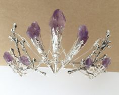 An entirely unusual and striking crown, which maintains the beauty of nature by using branches knitted together with wire, and suspending the smokey quartz shards against these, as though they could have grown there. The crown base is very slim, and can be fed into the hair and secured with pins. The main feature of the crown can be worn proudly standing, or flatter against the head to your choice. Smoky quartz is prized for its beauty, but also for its metaphysical properties. It promotes…