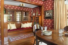 The dining room has new William Morris wallpaper and an original built-in bench with storage for table linens. The existing windows were mirrored after a bumpout at the back of the house blocked the view. Tables and chairs: @woodbridgefurn