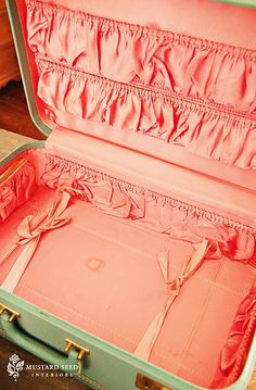 This vintage suitcase ~ green on the outside, salmon on the inside ~  My mom had a beige set with blue interior, I still have the little train box? or cosmetic box?