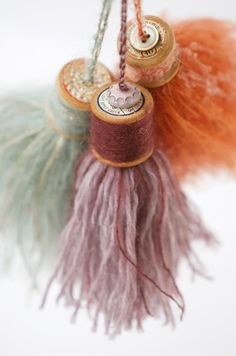 tassels made with vintage wooden spools and soft fiber with a little bling (buttons, jewels, etc.) added