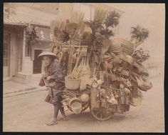 Peddler with cart full of bamboo baskets, brooms, and other merchandise c 1895. Attributed to Tamamura, Kozaburo (b.1856 d.1951)