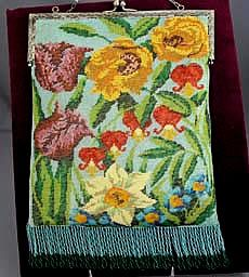 "A fine glass beaded purse with a bright blue background and a variety of floral decoration including poppies, lilies and other exotic flowers. Excellent condition and expertly relined with vintage trim.   Width: 7 1/4"". Length: 10"" with fringe."