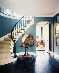thinking the entry, and stairs, and the dark flooring with blue walls, white trim would look like this picture    A curved staircase in a blue hallway