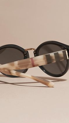 Round frame Burberry sunglasses in black acetate with check and camouflage arms.