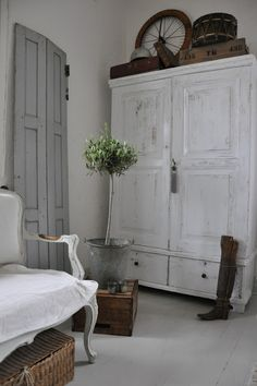 Paint an armoire white add grey walls, white slipcover for a favourite chair, a bit of wicker and some leather - the accessories on top of the armoire