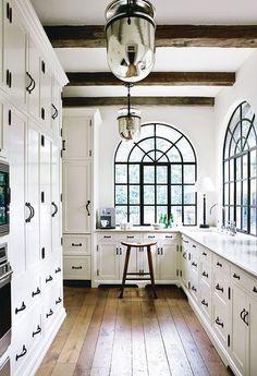 Light cabinetry with dark hardware and mercury glass lighting