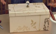 Storage box out of shoe box-covered in wall paper and knob added to top.  Could probably also decoupage scrapbook paper on to the box.  Cheap!