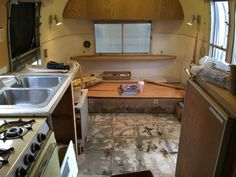 Kitchen with refrigerator, stove and sink. Living area at front of trailer.