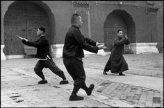 Henri Cartier-Bresson  CHINA. Beijing. December 1948. Each morning at dawn these men come to the Tai-miao Gardens to perform ritualistic exercises which serve not only to school the body, but also to discipline the mind to concentrate on matters of the spirit. In this group, there is a bank employee, a conservator of a museum, and an officer of the Kuomintang forces who does his exercises for two hours despite the steady advance of the Communist Army upon the walls of the city.