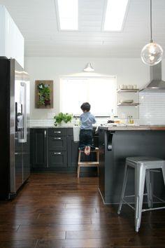 Black & white kitchen. Open shelves. White paneled ceiling. Wood floors. Walnut island. White granite counter.