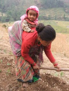 Baby wearing in Nepal. Mama gets her work done and baby is happy.