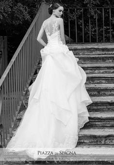 Effetto tatuaggio sulla schiena e gonna con strati di tulle in questo affascinante modello firmato Nadia Orlando. Guarda i suoi abiti da sposa su http://www.piazzadispagnasposi.it/collezioni/sposa/nadia-orlando-2017/