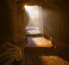 A tomb with stone steps leading to an empty burial bed and discarded wrappings. At the entrance the stone has been rolled away to reveal rays of sunlight and a partial view of outside the tomb.