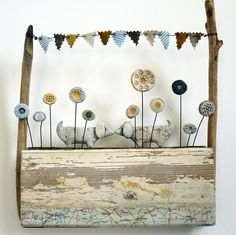 Shirley Vauvelle, Mixed Media Artist / Kissing Dashunds / Rub of noses and a kiss in the park flower bed. (Ceramic, driftwood and vintage map, 27cm x 30cm)