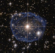 A large blue bubble with a bright star in the center on a black background filled with stars