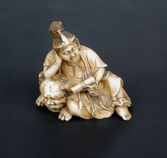 19th century ivory netsuke carved as a man, possibly Shubaka Sonja, seated holding a scroll, one elbow on the head of a reclining shishi