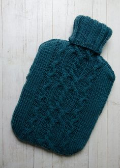 This cover is hand knitted to my own design, with a central twisted cable panel with bordering snake cables. The yarn is a soft acrylic and wool mix in a muted sea green. The ribbed neck allows easy filling without removing the cover, and a single pearly button on reverse allows cover to be removed for washing if needed.  Hand washable, or machine wash on wool cycle.  2 litre hot water bottle included