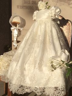 Christening Gown with Bonnet This gown boasts a very delicate lace, embroidered with silver thread and decorated with delicate Venetian trim on the sleeves and front bodice it also feature two satin r