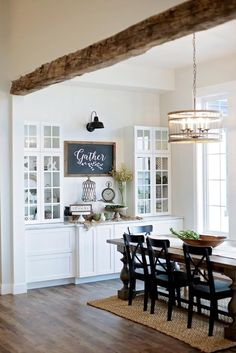 White built in storage display, rustic barn wood beam, vaulted ceiling, wood floors and farm table dining