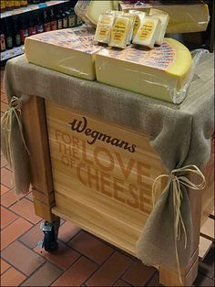 """A castered rolling island proclaims """"Wegmans For The Love of Cheese"""" as a philosophical and physical fact. Burlap tablecloth with ties, stacked wood crates, and Wegmans® Branded Wood Tray top off t… Wood Tray, Wood Crates, Rolling Island, Burlap Tablecloth, Visual Merchandising, Ties, Wheels, Advertising, Retail"""
