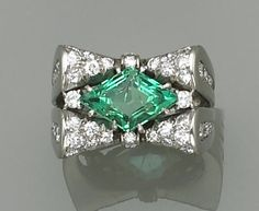 An art deco natural emerald, diamond and platinum ring  centering a lozenge-shaped emerald, in a rolled bow-tie motif, framed and accented on openwork shoulders by round brilliant-cut diamonds; emerald weighing an estimated: 2.20 carats.