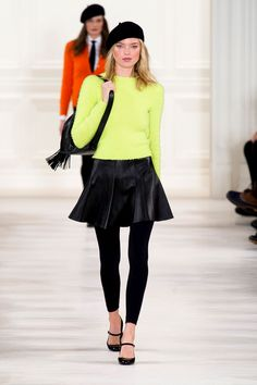 Ralph Lauren, New York Fashion Week Fall 2014. Neon pastel lime pullover, short shiny flared skirt in black, black leggings, strapped flats, black beret, fringed black hand bag.