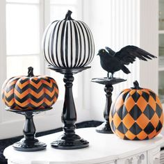 Spray paint dollar store glass candle sticks black and add pumpkins for Halloween decoration