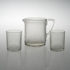 AINO AALTO AINO AALTO, A PITCHER AND TWO GLASSES. Model 4059, Karhula 1937-1938. Clear pressed glass. Height of the pitcher 14 cm. Height of the glasses 9 cm.