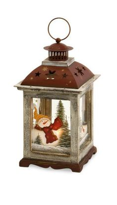 """The medium Snowman lantern has a hand painted snow scene on the glass with a rustic window pane look that adds a personal touch to Holiday decorating! Material: 40% Glass, 30% Firwood, 30% Iron. 13""""h x 7.25""""w x 7.25""""."""