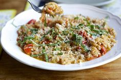 One-pan farro with tomatoes and onions | Smitten Kitchen  Hands off and abundantly rewarding, I recommend throwing in a few handfuls of some greens to wilt before adding the basil.