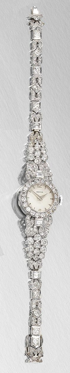 LADY'S DIAMOND COCKTAIL WATCH, 1950S AND A SAPPHIRE AND DIAMOND RING.  The circular dial applied with Arabic numerals and baton indicators, to a bezel set with circular-cut diamonds, on a tapered bracelet of foliate motif links set with step-, single- and circular-cut.
