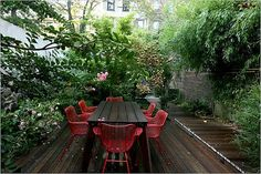 Small Urban Garden Design Ideas.. love the red chairs against the dark wooden deck & table