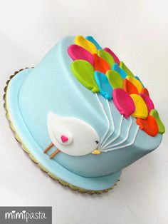 White chocolate&strawberry cake, decorated with coloured balloons, held by the little birdie.