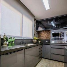 Cozinha com gabinetes e bancada cinza, puxadores escuros e superiores em vidro semitransparente. Parede em pastilha e ladrilho hidráulico. Cortina e gesso brancos.