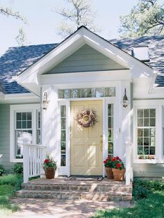love the color combo on this cottage, yellow front door, warm sea foam green