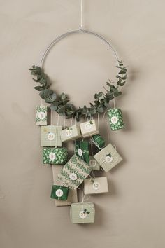 How to make your own Advent calendar. Decorate a metal ring with eucalyptus. Wrap the gifts in beautiful papers and hang them from the wreath. Find Christmas wrapping paper, tags, decorations and more DIY inspiration on our website.  #DIY #panduro #advent #christmas #jul #adventskalender #julkalender #pakkekalender #julekalender