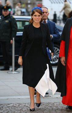 Princess Eugenie looked elegant wearing an asymmetric black dress with a white tapered detail, she paired it with a simple black jacket and added a flash of color in the form of blue felt hat as she arrived the evening service at Westminster Abbey.