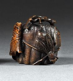 """WOOD NETSUKE 19th Century  By Toyomasa. In the form of a wasp and wasp''s nest with inlays of bone and pewter. Signed. Length 1.3""""."""