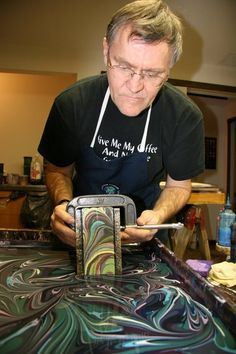 Daniel J. St. John edges a book using the process of marbling. He and his wife Regina are owners of Chena River Marblers in Amherst, MA.